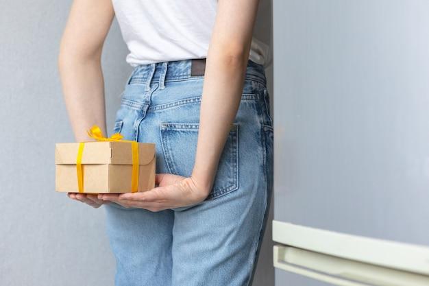 Vrouw met kraft-kartonnen dozen met gele strik of lint, voedsel of kleding op moderne manieren bezorgd