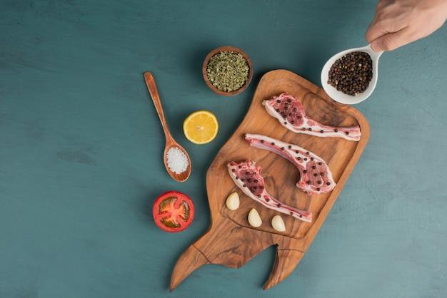 Vrouw met kruiden kom en stukken ongekookt vlees op blauwe tafel.