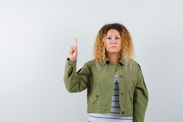 Vrouw met krullend blond haar die eureka-gebaar toont, omhoog in groen jasje wijst en intelligent, vooraanzicht kijkt.
