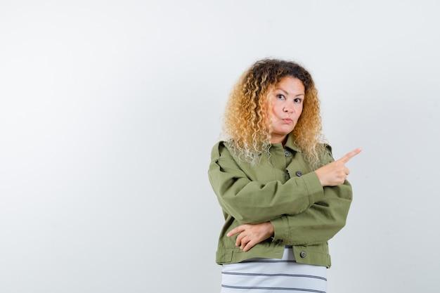 Vrouw met krullend blond haar die naar de rechterbovenhoek in groen jasje wijst en aarzelend kijkt. vooraanzicht.
