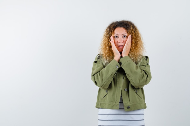 Vrouw met krullend blond haar handen op de wangen in groene jas houden en opgewonden kijken. vooraanzicht.