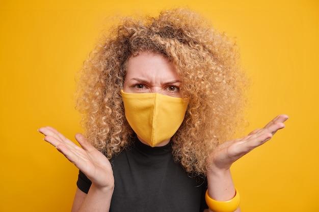 Vrouw met krullend borstelig haar draagt beschermend gezichtsmasker spreidt handpalmen zijwaarts beschermt zichzelf tegen coronavirus