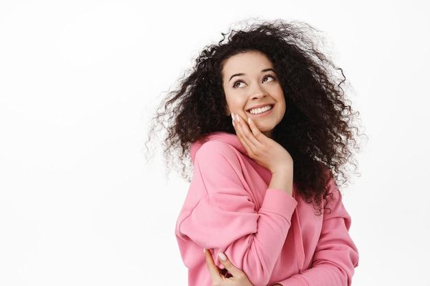 Vrouw met krullend donker haar, haar gezicht aanrakend, glimlachend en opzij starend naar wit