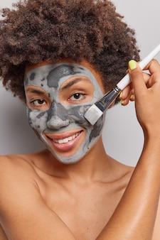Vrouw met krullend haar brengt een klei-voedend gezichtsmasker aan met een cosmetische borstel glimlacht en poseert zachtjes topless op wit