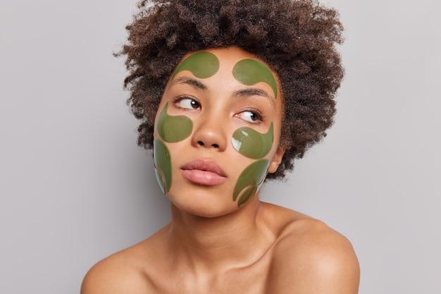 Vrouw met krullend haar brengt groene schoonheidspatches aan en staat blote schouders op grijs