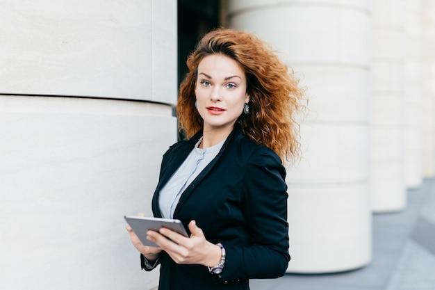 Vrouw met krullend haar dat zwart kostuum en witte blouse draagt, die tabletcomputer houdt