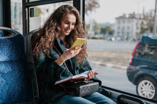 Vrouw met krullend haar die met de bus reist