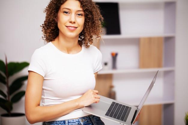 Vrouw met krullend haar die op laptop in het bureau werkt.