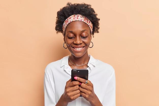 Vrouw met krullend haar gebruikt mobiele telefoon chats online krijgt bericht van vriend draagt hoofdband oorbellen wit overhemd geïsoleerd op beige