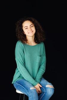 Vrouw met krullend haar gekleed in een stijlvolle trui en jeans zit op een stoel