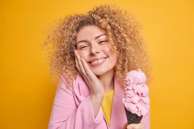 Vrouw met krullend haar houdt hand op de wang glimlacht zachtjes houdt lekker ijsje voelt de verleiding om zoet koud dessert te eten drukt geluk uit