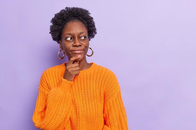 Vrouw met krullend haar houdt hand op kin heeft peinzende uitdrukking denkt dat iets oranje gebreide trui draagt geïsoleerd op paars