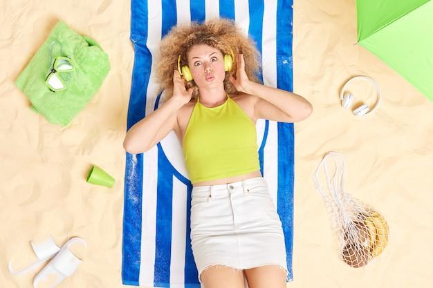 Vrouw met krullend haar houdt lippen gevouwen luistert muziek via koptelefoon ligt op handdoek aan zandstrand gekleed in zomerkleren geniet van goede rust houdt lippen gevouwen. recreatietijd