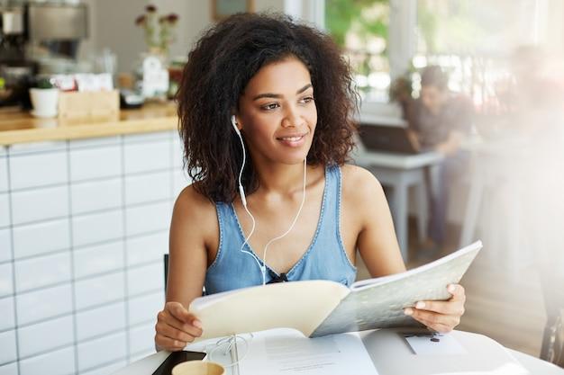 Vrouw met krullend haar in casual kleding zitten in de cafetaria, koffie drinken, muziek in de koptelefoon luisteren, op zoek naar papieren voor werk.