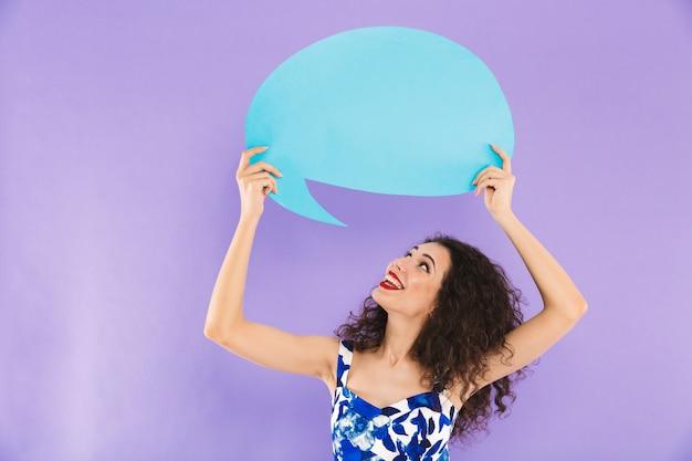 Vrouw met krullend haar in kleding die en commerciële bel boven haar hoofd glimlacht houdt