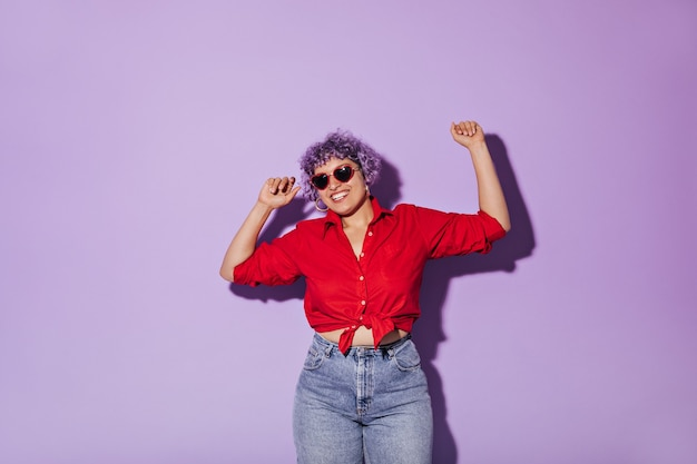 Vrouw met krullend haar in zonnebril, rood shirt met lange mouwen en spijkerbroek glimlacht op paars. charmante vrouw in stijlvolle kleding poseren