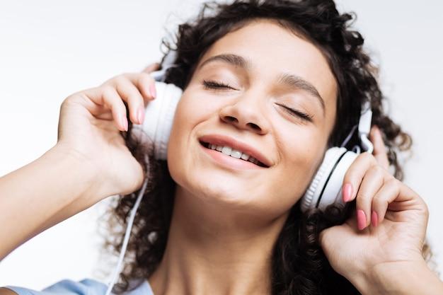 Vrouw met krullend haar luistert naar de muziek in witte koptelefoons en drukt ze tegen haar oren terwijl ze haar ogen in verrukking sluit