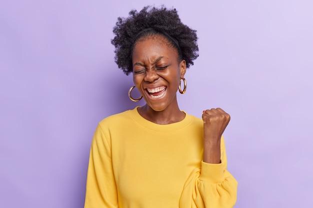Vrouw met krullend haar maakt ja gebaar voelt alsof winnaar vuist opheft draagt gele trui en oorbellen geïsoleerd op paars