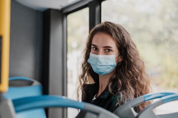 Vrouw met krullend haar medische masker dragen in de bus