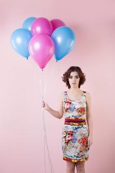 Vrouw met krullend haar met ballonnen