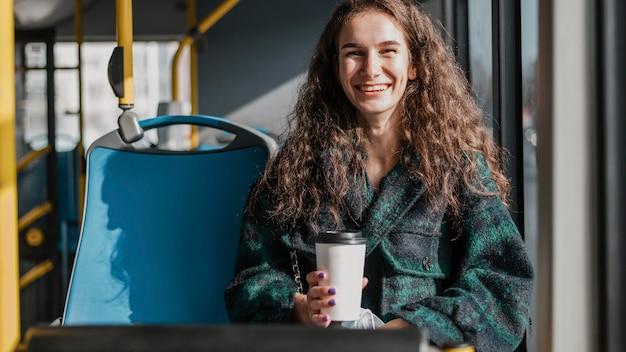 Vrouw met krullend haar met een kopje koffie in de bus