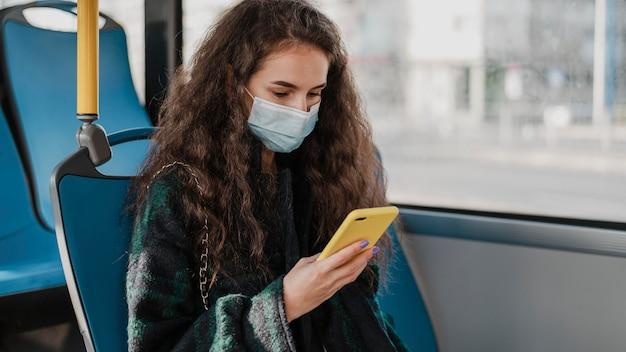 Vrouw met krullend haar met haar mobiele telefoon in de bus