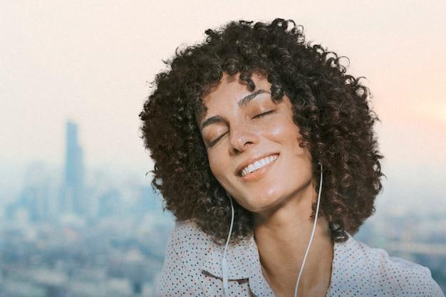 Vrouw met krullend haar met koptelefoon remixed media met uitzicht op de stad
