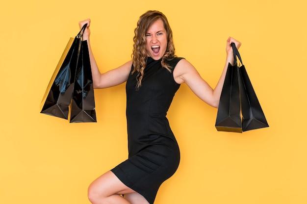 Vrouw met krullend haar met zwarte boodschappentassen
