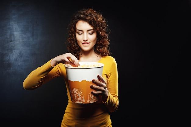 Vrouw met krullend haar neemt wat popcorn in haar onderlip bijten