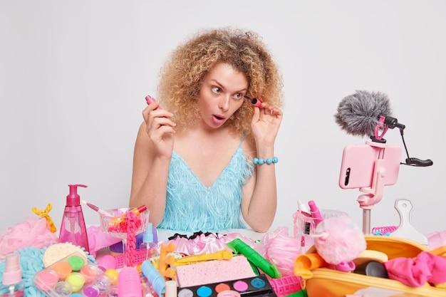 Vrouw met krullend haar past mascara-records toe, livestreamvideo geeft aanbeveling hoe ze make-up moet doen voor haar vlog, omringd door verschillende cosmetische producten die op een witte muur zijn geïsoleerd. schoonheidsvlogger