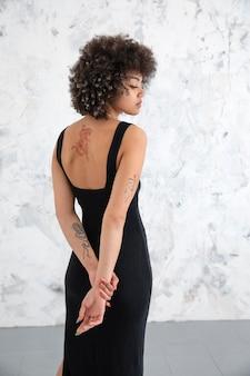 Vrouw met krullend haar poseren op een zelfverzekerde manier