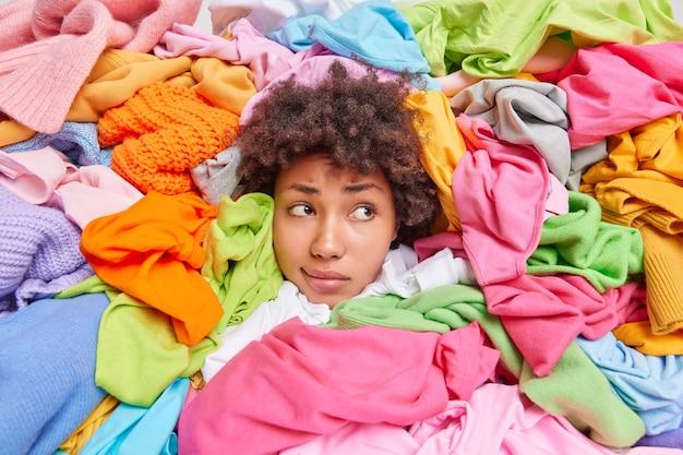 Vrouw met krullend haar verzamelt kledingstukken in goede staat naar consignatiewinkel of kringloopwinkel omringd door enorme stapels veelkleurige kledingstukken die weggefocust zijn en heeft een vermoeide uitdrukking. textiel recyclen