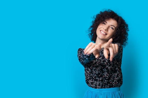 Vrouw met krullend haar wijst naar de camera en glimlacht op een blauwe muur met vrije ruimte