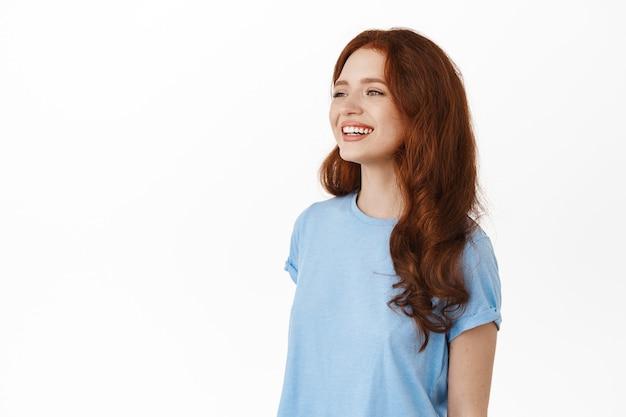 Vrouw met krullend kapsel, gekleed in vrijetijdskleding, naar links kijkend met een blij zorgeloos gezicht, pratend met iemand, staande op wit
