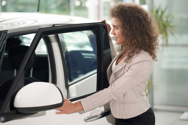Vrouw met krullende haar openingsdeur van witte auto.