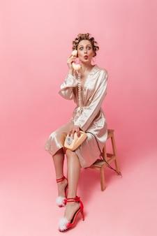 Vrouw met krulspelden gekleed in gewaad zit op een stoel en spreekt verbaasd aan de telefoon
