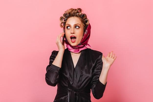 Vrouw met krulspelden gekleed in zijden gewaad en sjaal praten over de telefoon