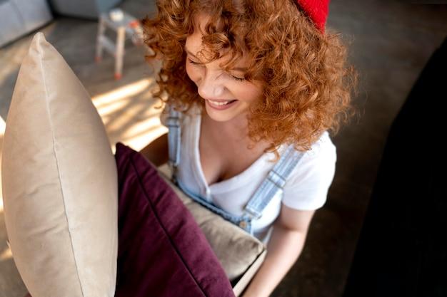 Vrouw met kussens voor het inrichten van een nieuw huis