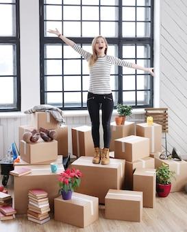 Vrouw met lading pakketten klaar voor verzending of verplaatsen, staan en lachen