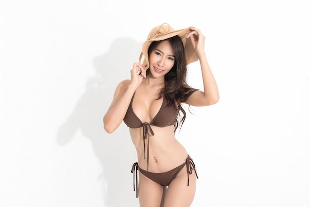 Vrouw met lang bruin haar, gekleed in een bruine bikini jurk en zonnehoed op een zomerse manier op wit en schaduw.