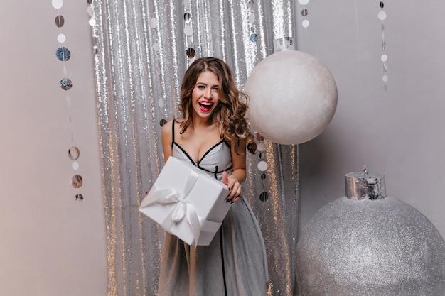 Vrouw met lang donker haar en mooie make-up in goed humeur op kerstfeest. portret van een dame die een vakantiegift heeft ontvangen