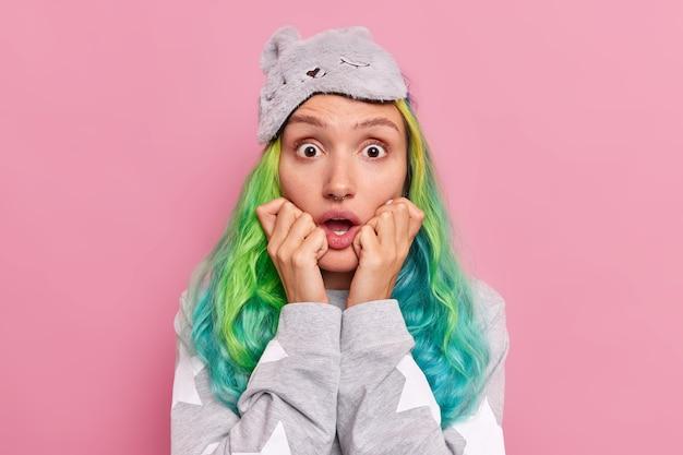 Vrouw met lang geverfd haar staart verwarde ogen houdt mond open handen op gezicht draagt slaapmasker en pyjama poses op roze