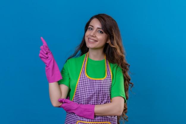 Vrouw met lang golvend haar die schort en rubberhandschoenen draagt die naar de kant met vinger glimlachen die vriendelijk status op blauw glimlachen