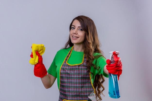 Vrouw met lang golvend haar die schort en rubberhandschoenen dragen die kleed houden en het schoonmaken nevel die positief glimlachen zelfverzekerd status kijken