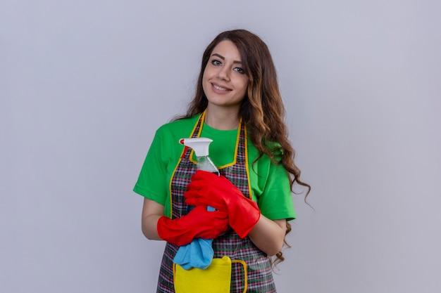 Vrouw met lang golvend haar die schort en rubberhandschoenen dragen die schoonmakende nevel met glimlach op gezicht status houden