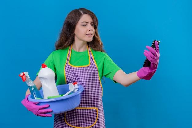 Vrouw met lang golvend haar draagt een schort en rubberen handschoenen met een kom vol met schoonmaakgereedschap kijkend naar mobiele telefoon met verwarde uitdrukking staande op blauw