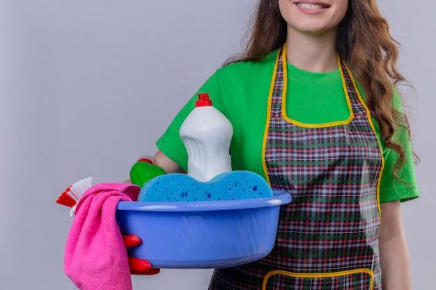 Vrouw met lang golvend haar, het dragen van schort en rubberen handschoenen staan met bekken vol met schoonmaak tools glimlachen
