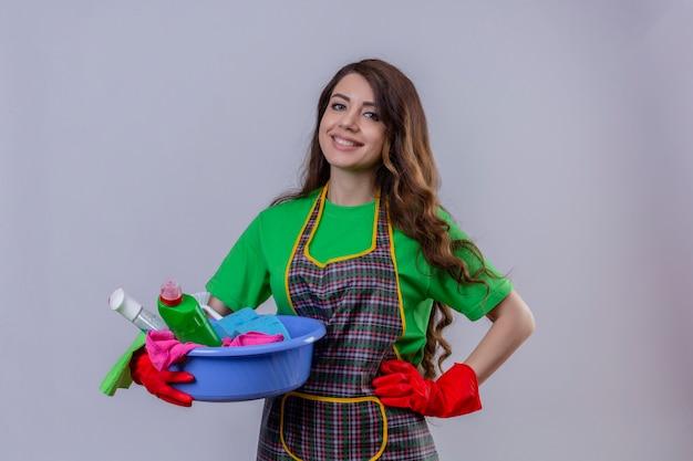 Vrouw met lang golvend haar, het dragen van schort en rubberen handschoenen staan met bekken vol met schoonmaakmiddelen glimlachend vriendelijk met blij gezicht