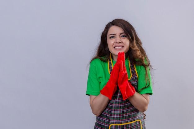 Vrouw met lang golvend haar schort en rubberen handschoenen dragen bedelen en bidden met handen samen met hoop uitdrukking op gezicht staan
