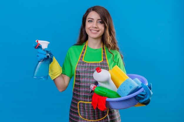 Vrouw met lang golvend haar schort en rubberen handschoenen dragen bekken met schoonmaakproducten en spray met blij gezicht lachend op blauw te houden